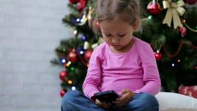 Menina bonito pequena que usa o telefone esperto, na frente da árvore de Natal Tiro do close-up vídeos de arquivo