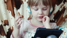 Menina bonito pequena que usa a tabuleta digital video estoque