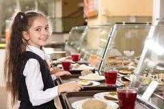 Menina bonito perto de servir a linha com alimento saudável na cantina foto de stock