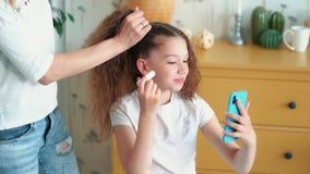 A menina bonito pinta seus bordos com batom quando a mãe pentear seu cabelo, movimento lento