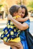 Menina bonito que abraça seu tiro exterior da mãe no parque fotos de stock