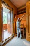 Menina bonito que abre a porta deslizante de vidro grande ao balcão foto de stock royalty free