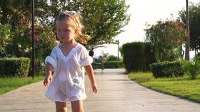 Menina bonito que anda no trajeto do parque filme