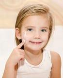 Menina bonito que aplica o creme Foto de Stock Royalty Free