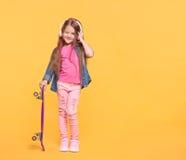 Menina bonito que aprecia a música usando auscultadores Fotografia de Stock Royalty Free