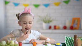 Menina bonito que aprecia o gosto e o aroma do coelho do chocolate, sonhando sobre o animal de estimação filme
