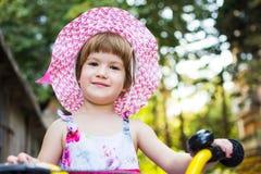 Menina bonito que aprende montar uma bicicleta foto de stock