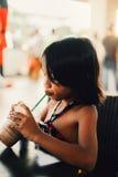 Menina bonito que bebe a agitação de chocolate gelado em um café Fotografia de Stock Royalty Free