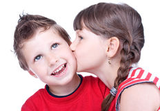 Menina bonito que beija um menino eyed azul Foto de Stock