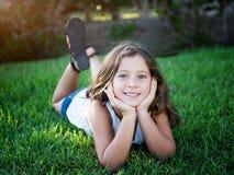 Menina bonito que coloca na grama Fotografia de Stock Royalty Free