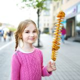Menina bonito que come a batata fritada em uma vara Imagens de Stock Royalty Free