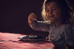Menina bonito que come cerejas para seu café da manhã da manhã fotografia de stock royalty free