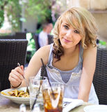 Menina bonito que come a massa no café ao ar livre Fotos de Stock Royalty Free