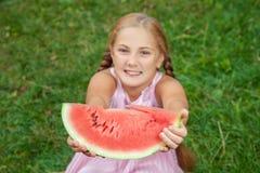Menina bonito que come a melancia na grama nas horas de verão com cabelo longo do rabo de cavalo e o sorriso toothy que sentam-se Fotos de Stock