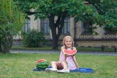 Menina bonito que come a melancia na grama nas horas de verão com cabelo longo do rabo de cavalo e o sorriso toothy que sentam-se Fotos de Stock Royalty Free