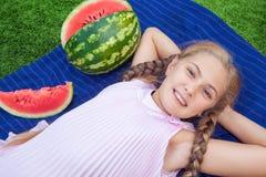 Menina bonito que come a melancia na grama nas horas de verão com cabelo longo do rabo de cavalo e o sorriso toothy que sentam-se Imagens de Stock Royalty Free