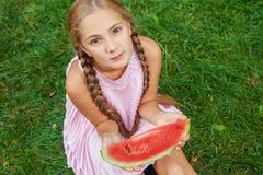 Menina bonito que come a melancia na grama nas horas de verão com cabelo longo do rabo de cavalo e o sorriso toothy que sentam-se Fotografia de Stock