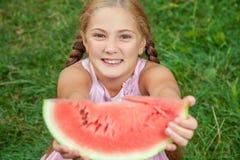 Menina bonito que come a melancia na grama nas horas de verão com cabelo longo do rabo de cavalo e o sorriso toothy que sentam-se Imagens de Stock