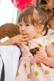 Menina bonito que come o bolo com crosta de gelo em sua cara foto de stock royalty free