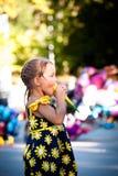 Menina bonito que come o gelado no dia de verão do parque foto de stock