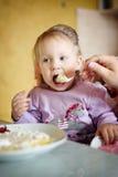 Menina bonito que come o papa de aveia Imagem de Stock