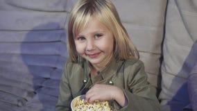 Menina bonito que come a pipoca que sorri à câmera no cinema imagem de stock royalty free