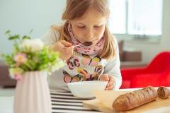 Menina bonito que come a sopa com p?o inteiro da gr?o em casa imagens de stock royalty free