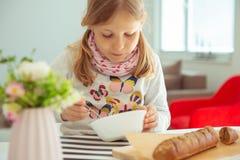 Menina bonito que come a sopa com p?o inteiro da gr?o em casa fotografia de stock