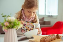 Menina bonito que come a sopa com p?o inteiro da gr?o em casa foto de stock royalty free