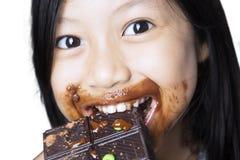 Menina bonito que come um chocolate no estúdio Imagem de Stock