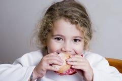 Menina bonito que come um sanduíche Fotografia de Stock Royalty Free