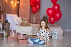 Menina bonito que comemora o dia do nascimento junto perto dos balões vermelhos Cena bonita da menina no vestido azul fotografia de stock royalty free