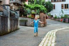 Menina bonito que corre ao longo da rua em uma vila pequena Fotografia de Stock Royalty Free