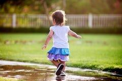 Menina bonito que corre através das poças Fotografia de Stock Royalty Free