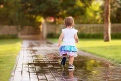 Menina bonito que corre através das poças Foto de Stock