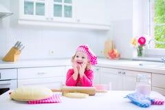 Menina bonito que coze uma torta Fotografia de Stock Royalty Free