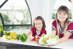 Menina bonito que cozinha com sua irmã, alimento saudável Fotografia de Stock