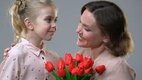 Menina bonito que dá flores à mãe amado, surpresa para o aniversário ou o 8 de março vídeos de arquivo