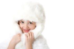 Menina bonito que desgasta um casaco de pele e um chapéu brancos fotos de stock royalty free