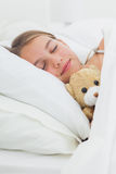 Menina bonito que dorme com seu urso de peluche Fotografia de Stock
