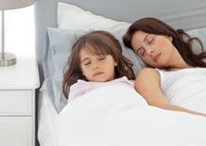 Menina bonito que dorme com sua matriz foto de stock