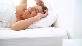 Menina bonito que dorme na cama que acorda o esticão e o sorriso vídeos de arquivo