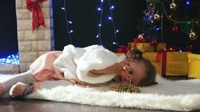 Menina bonito que encontra-se e que joga perto do ireplace, árvore de Natal decorada vídeos de arquivo