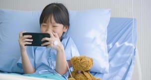 Menina bonito que encontra-se na cama no hospital, desenhos animados engraçados de observação, filmes no smartphone Doença e trat vídeos de arquivo