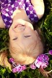 Menina bonito que encontra-se na grama no parque Ch agradável de sorriso Imagens de Stock Royalty Free