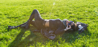 Menina bonito que encontra-se na grama verde e que relaxa sob o sol Fotografia de Stock