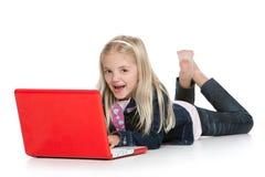 Menina bonito que encontra-se para baixo com riso do portátil fotos de stock