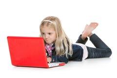 Menina bonito que encontra-se para baixo usando um portátil imagem de stock
