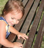 A menina bonito que escala sobre um parque de madeira seja Fotografia de Stock