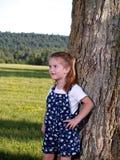 Menina bonito que esconde atrás da árvore Fotos de Stock Royalty Free